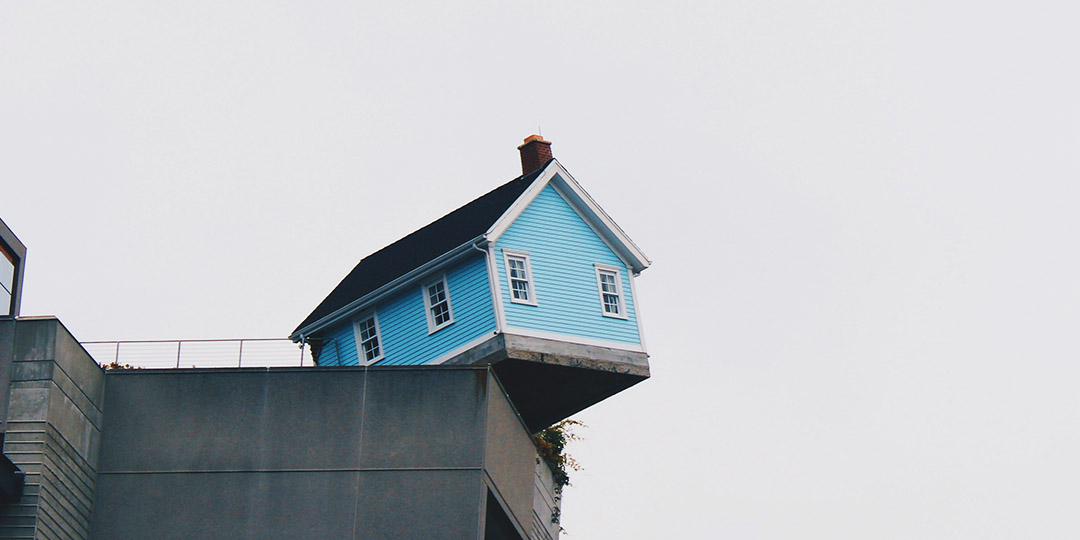 blue house on the edge of a cliff
