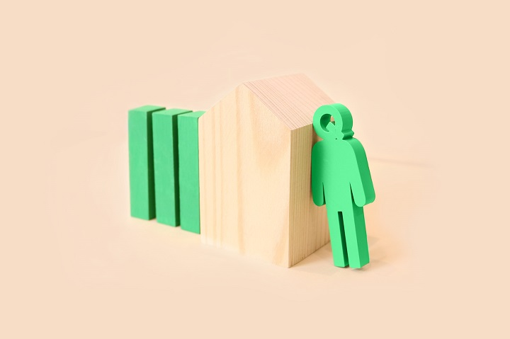 green queue man resting on beige wooden building block