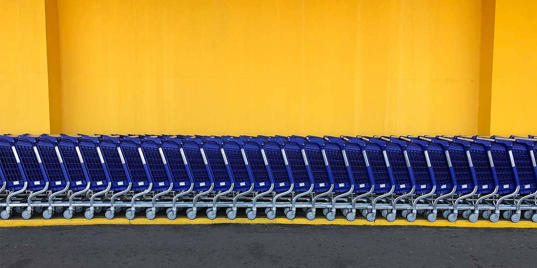 Blue shopping carts against yellow background