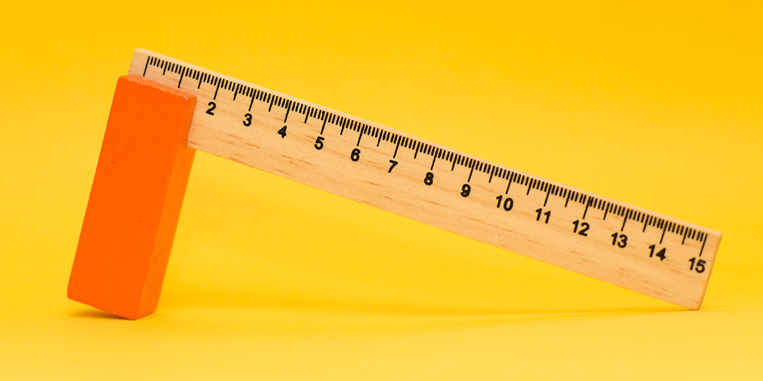 Wooden measuring ruler on yellow background