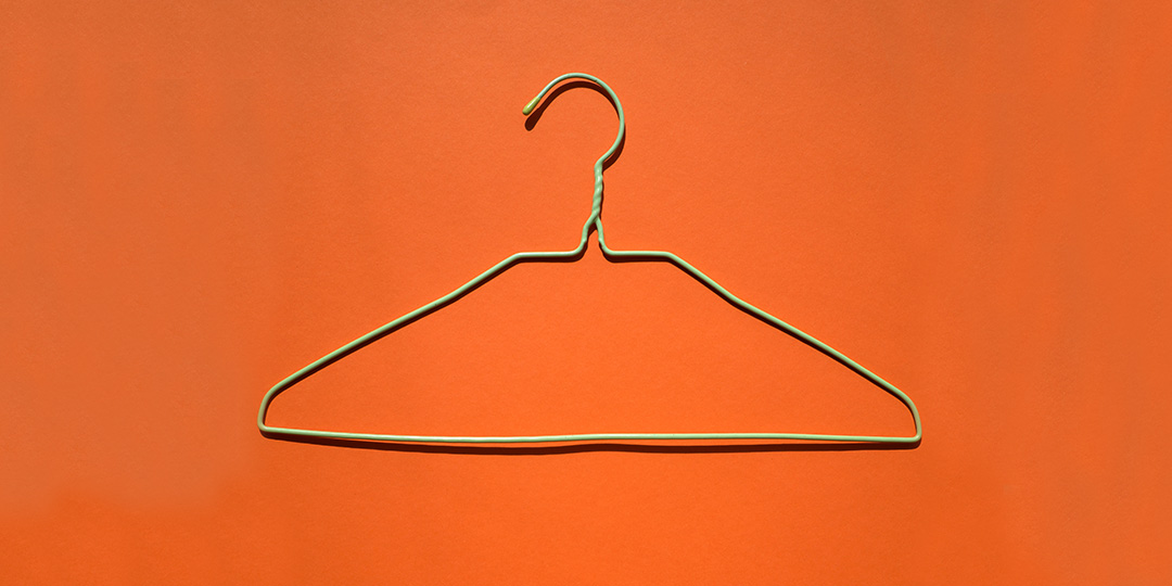 green clothes hanger on orange background