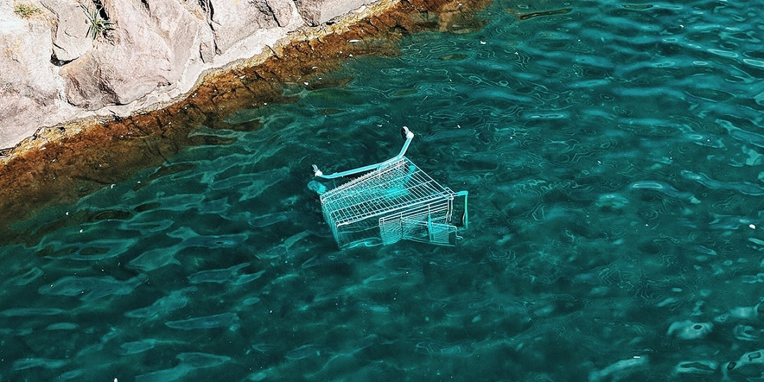 Shopping cart sinking in blue water