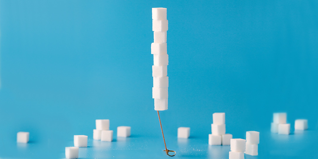 Stack of sugar cubes on blue background