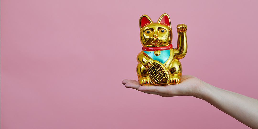 Golden toy cat waving with pink background