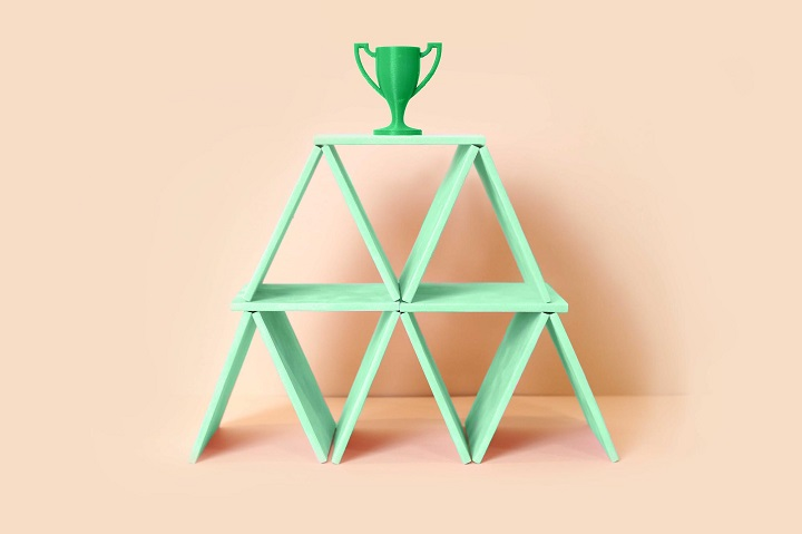 Green trophy on top of green card pyramid