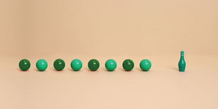 Green bowling balls headed towards bowling pin